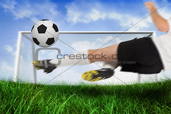 Football player in white kicking the ball