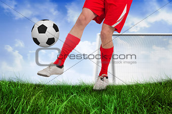 Fit football player kicking the ball