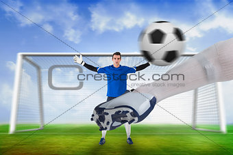 Football player striking ball at goalkeeper