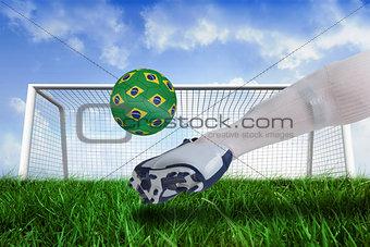 Close up of football player kicking brasil ball