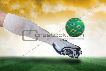 Close up of football player kicking brazil ball