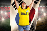 Excited football fan in brasil tshirt holding south korea flag