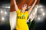 Pretty football fan in brasil t-shirt holding ivory coast flag