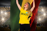 Excited football fan in brasil tshirt holding ghana flag