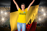 Excited football fan in brasil tshirt holding belgium flag