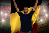 Excited football fan in black cheering holding belgium flag