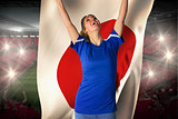 Cheering football fan in blue jersey holding japan flag