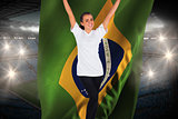 Excited football fan in white cheering holding brasil flag