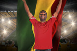 Excited handsome football fan cheering holding ghana flag