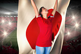 Cheering football fan in red holding japan flag