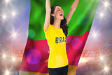 Excited football fan in brasil tshirt holding cameroon flag