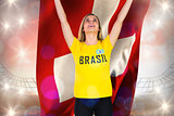 Excited football fan in brasil tshirt holding swiss flag