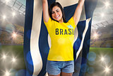 Excited football fan in brasil tshirt holding greece flag