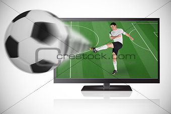 Football player in white kicking ball out of tv