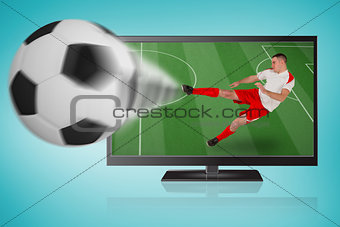 Fit football player playing and kicking ball out of tv