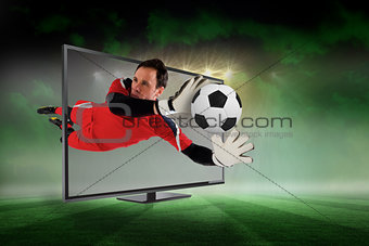 Fit goal keeper saving goal through tv