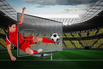 Fit football player kicking ball through tv