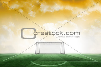 Football pitch and goal under yellow sky