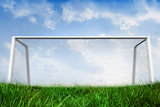 Goalpost on grass under blue sky