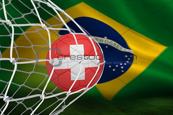 Football in swiss colours at back of net