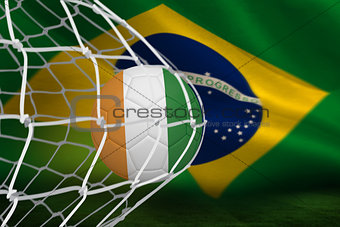 Football in ivory coast colours at back of net