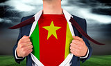 Businessman opening shirt to reveal cameroon flag