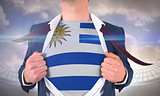 Businessman opening shirt to reveal uruguay flag
