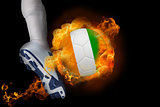 Football player kicking flaming ivory coast ball