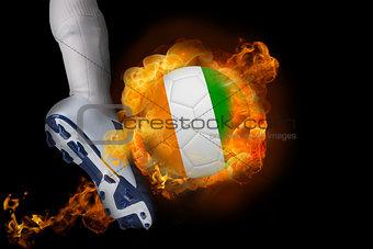 Football player kicking flaming ivory coast ball