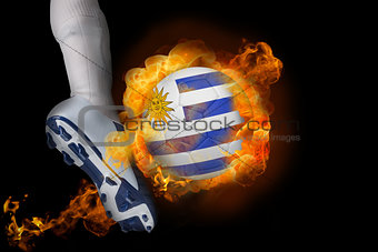 Football player kicking flaming uruguay ball