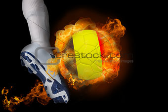 Football player kicking flaming belgium ball