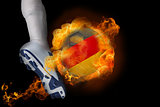Football player kicking flaming germany ball