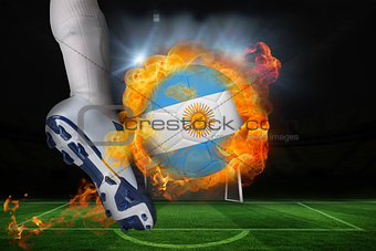 Football player kicking flaming argentina flag ball