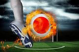 Football player kicking flaming japan flag ball