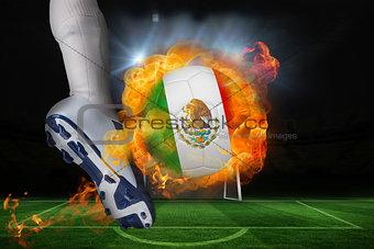 Football player kicking flaming mexico flag ball