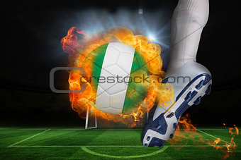 Football player kicking flaming nigeria flag ball
