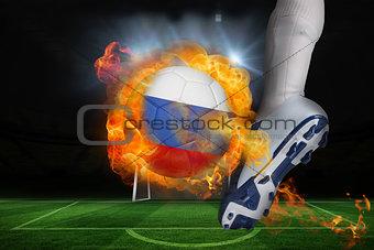 Football player kicking flaming russia flag ball