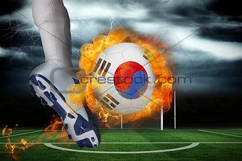 Football player kicking flaming south korea flag ball