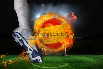 Football player kicking flaming spain flag ball