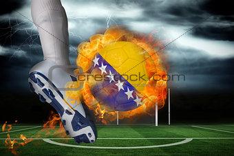 Football player kicking flaming bosnia flag ball