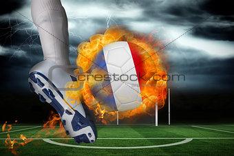 Football player kicking flaming france flag ball