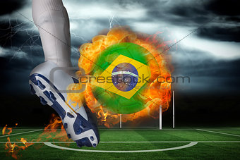 Football player kicking flaming brasil flag ball