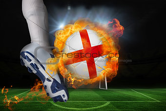 Football player kicking flaming england flag ball