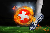 Football player kicking flaming swiss flag ball