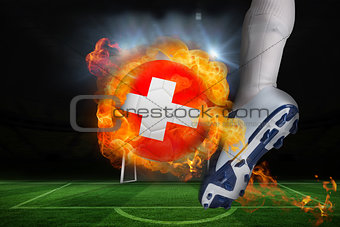 Football player kicking flaming swiss flag ball