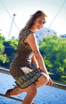 beautiful woman sitting on parapet