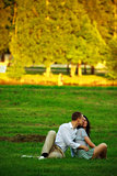 young couple sitting on park lawn