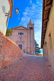 Old church and narrow street. Monticello D'Alba, Italy.