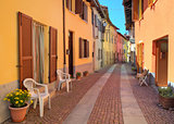 Narrow cobbled street among colorful houses in Italy.