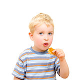 Cute little boy eating delicious cookie isolated on white